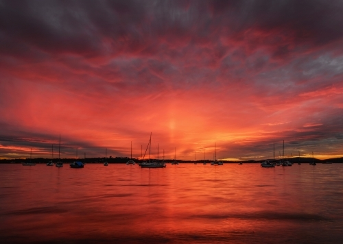 Dramatic red sunset behind yachts moored at Roy Wood Reserve, Port Stephens
