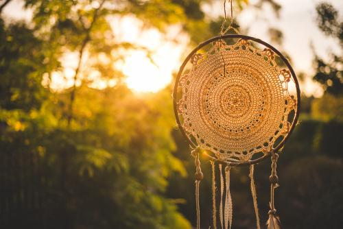Dreamcatcher against a sunset and green trees