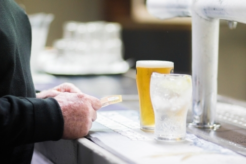 Man paying for glass of beer at the bar