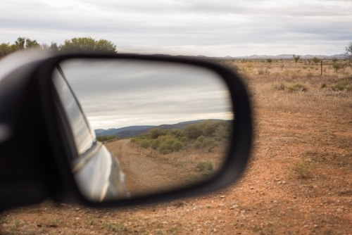 Driving, looking at reflection in side window of remote country