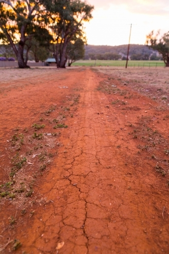 Dry red cracked earth path on a rural property at dusk