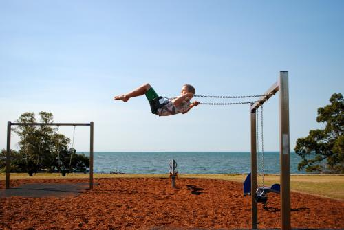 Boy on a swing in a playground near the sea
