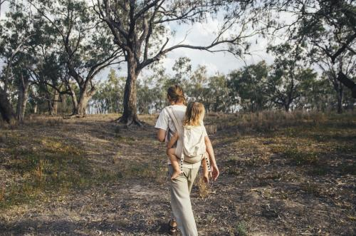 Father and daughter walking through bushland