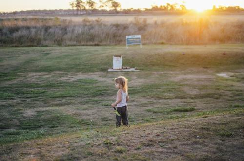 Young girl standing on rural golf course at sunset