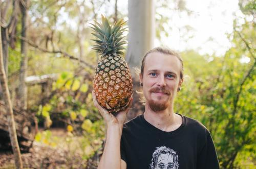 Young man smiling with a pineapple in the bush