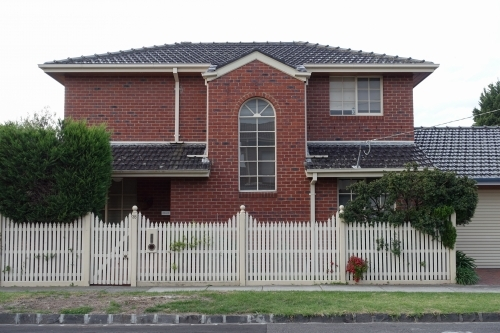A double story suburban brick home with picket fence