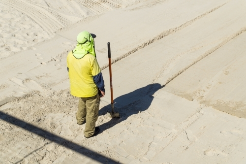A council worker with his shovel stands on a white sand beach