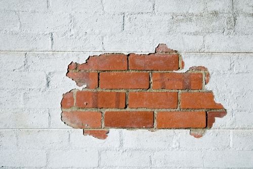 Paint peeling from a white wall showing red bricks