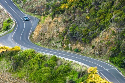 Looking down on a  car driving on a winding road in the hills