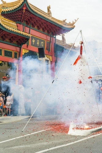 A cloud of smoke rising from a string of firecrackers going off in front of a Chinese building