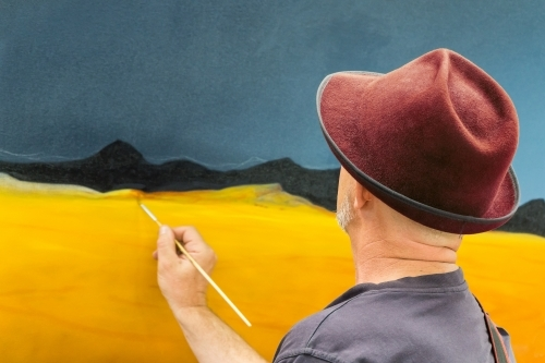 Looking over the shoulder of an artist painting a canvas