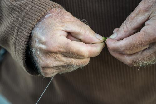 Close up of an old man's hands baiting a fishing hook