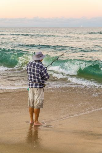 A fisherman standing on a beach as waves crash onto shore