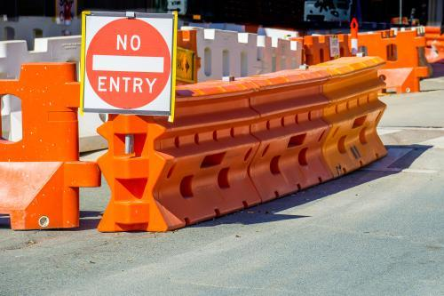"Large orange barriers and a ""no entry"" sign on a road"