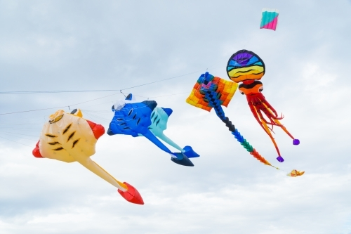 A string of colourful kites flying in the sky