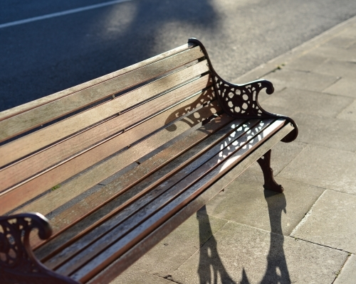 A classic wooden public bench in the afternoon sun
