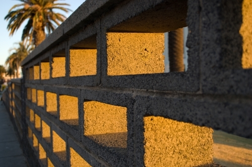 A cinder block brick wall bathed in golden light