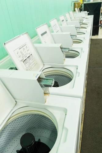 A row of washing machines with their lids up in a launderette