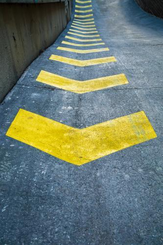 A row of yellow safety arrows painted on a road