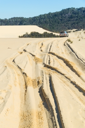 A four wheel drive leaving tracks in sand dunes