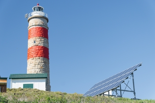 A stone lighthouse on a hill next to an array of solar panels