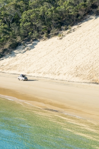 A 4WD driving along a beach below a sand dune