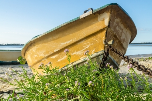Ground level view of an old row boat chained up on the beach