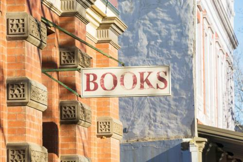 "An old fashion ""books"" sign hangs from a historic brick building"
