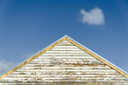 The peak of a tin roof and weatherboard house against a blue sky