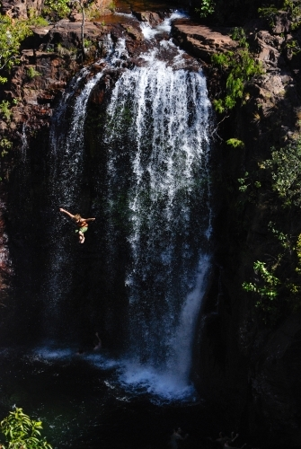 A man in mid air after jumping off a very high waterfall