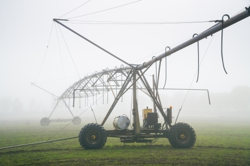 A large irrigation sprinkler in a paddock on a foggy morning