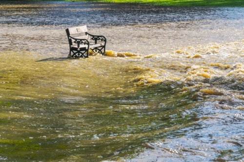 A park bench sits in rushing flood waters