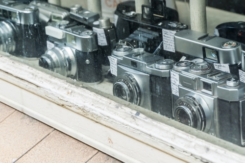 A collection of old cameras in a shop window