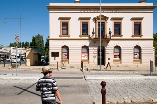 Boy stands outside of a historic building in regional Australia