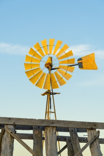 Close up of a windmill and the top of an old wooden tank stand