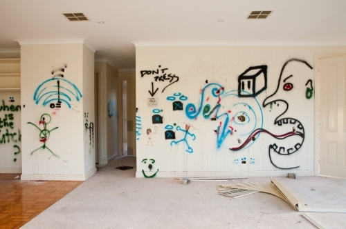 An empty, modern house with graffiti on the walls