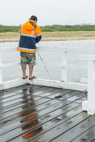 A man fishing over a jetty railing in wet weather