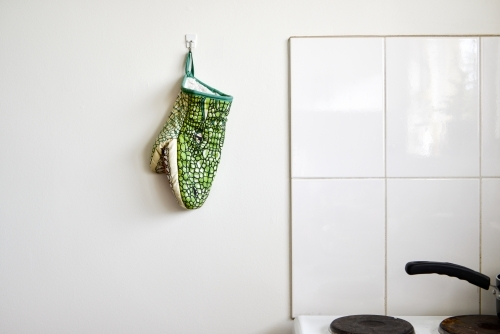 Crocodile oven glove hanging on a white kitchen wall