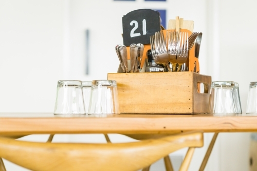 A wooden table in a restaurant with cutlery and glasses sitting on it