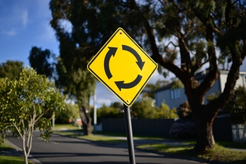 A yellow roundabout street sign bathed in sunlight