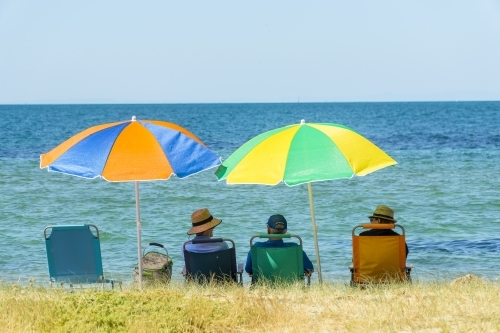 People sitting in beach chairs under colourful umbrellas