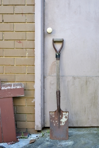 A rusty old spade leaning against a garage door