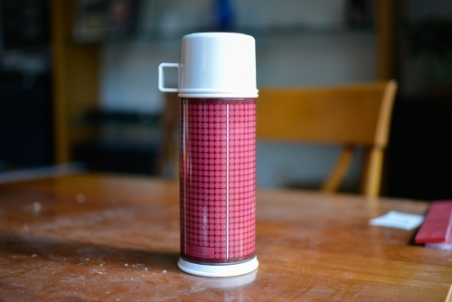 A thermos flask sits on a table during a renovation