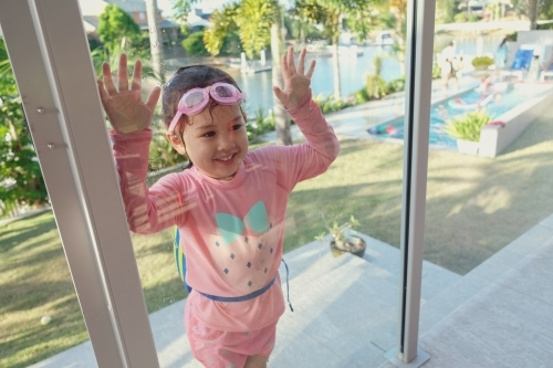 Little girl by pool glass fencing