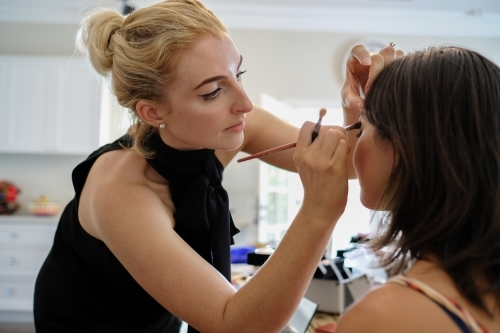 Makeup artist applying makeup on a woman, work from home