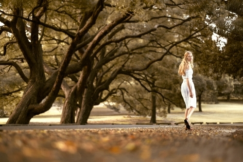 Lady walking amongst the trees in a white dress during autumn