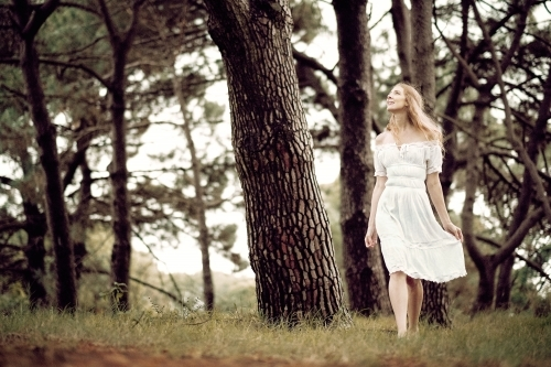 Young lady walking in the woods in a white dress