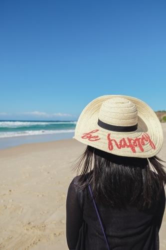 Female wearing be happy hat on the beach