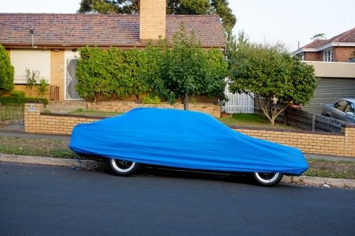 A car parked on the street under a blue cover