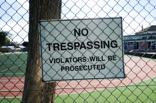 No trespassing sign attached to a large fence